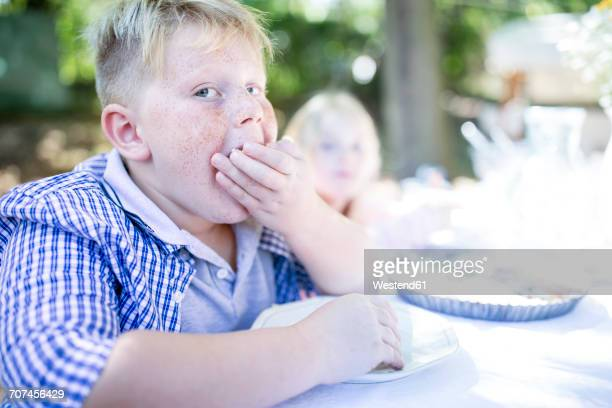 Portrait of boy eating at garden table