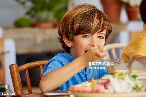 portrait of boy eating food at table in house - one boy only stock pictures, royalty-free photos & images