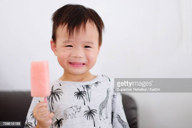 Portrait Of Boy Eating Popsicle While Standing At Home