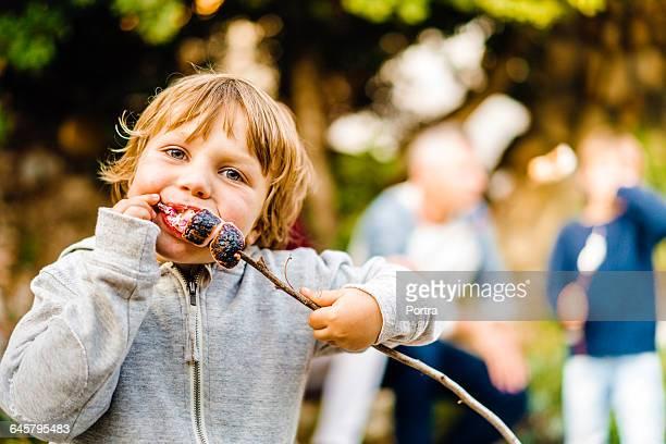 Portrait of boy eating roasted marshmallows