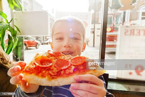 Portrait of boy eating slice of pizza