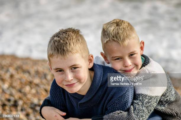 Portrait Of Boy Embracing Twin Brother At Beach