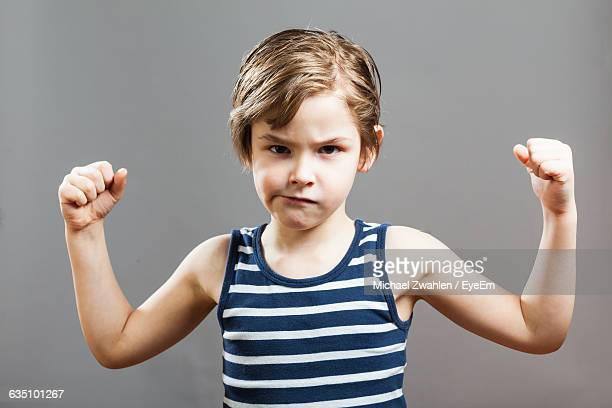 Portrait Of Boy Flexing Muscles Against Gray Background