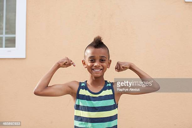 portrait of boy flexing muscles - mohawk stock photos and pictures