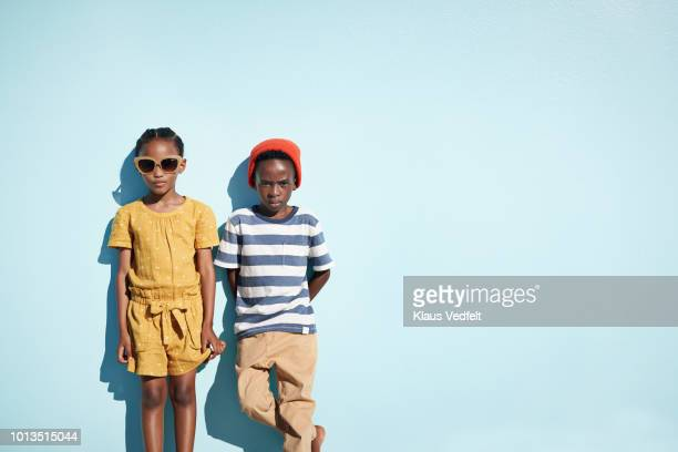 portrait of boy & girl holding hands and looking in camera, on blue backdrop in summer - side by side stock pictures, royalty-free photos & images