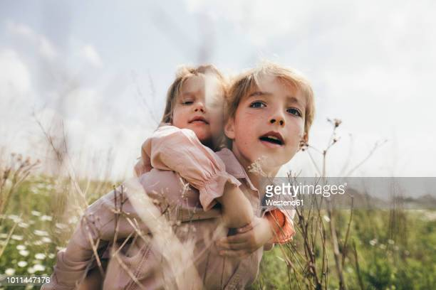 portrait of boy giving his little sister a piggyback ride - 10 11 jaar stockfoto's en -beelden
