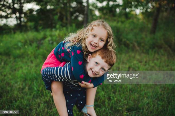 Portrait of boy giving sister a piggyback in field