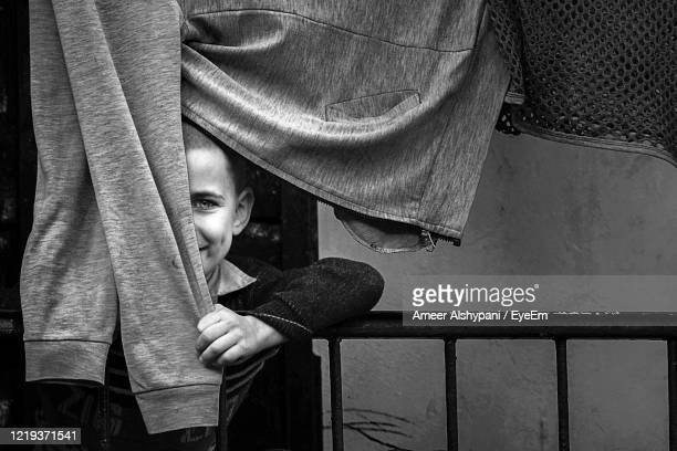 portrait of boy hiding behind cloth - iraq stock pictures, royalty-free photos & images