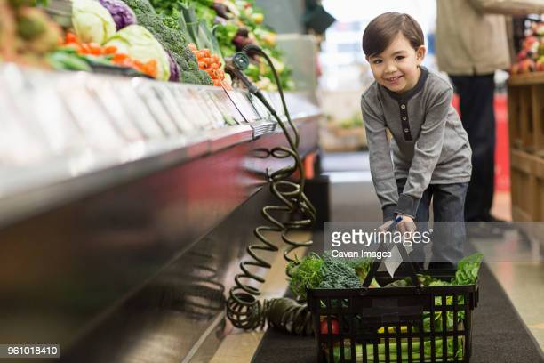 portrait of boy holding basket while standing by shelves at supermarket - cavan images foto e immagini stock
