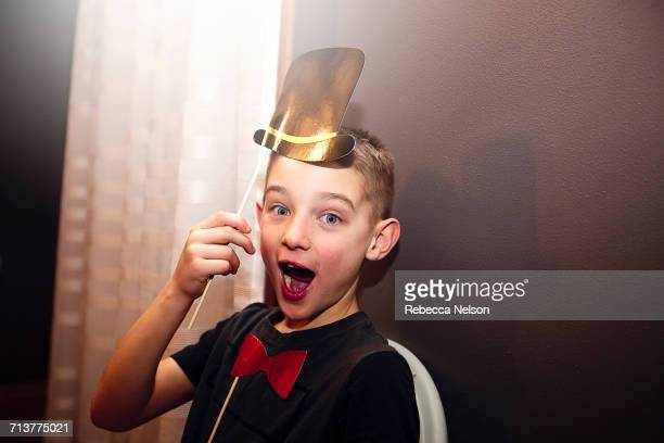 Portrait of boy holding bow tie and top hat stick masks posing at party