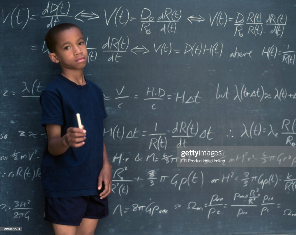 Portrait of boy holding chalk while standing in front of chalkboard : Stock Photo