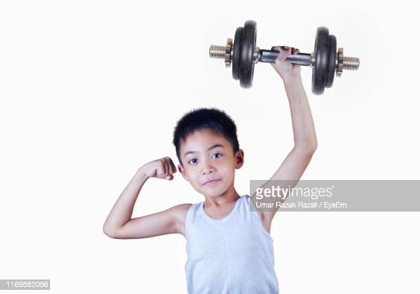 portrait of boy holding dumbbell against white background - kids weightlifting ストックフォトと画像