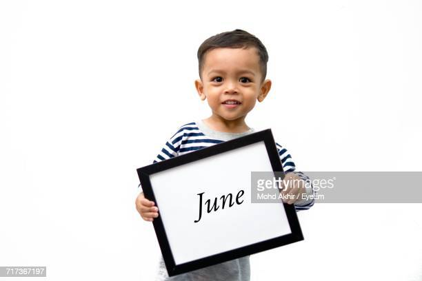 Portrait Of Boy Holding Frame With June Text Against White Background