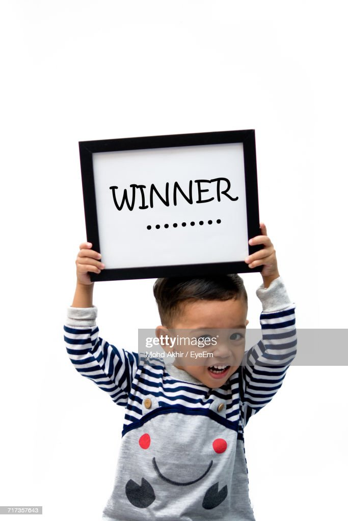 Portrait Of Boy Holding Frame With Winner Text Against White ...