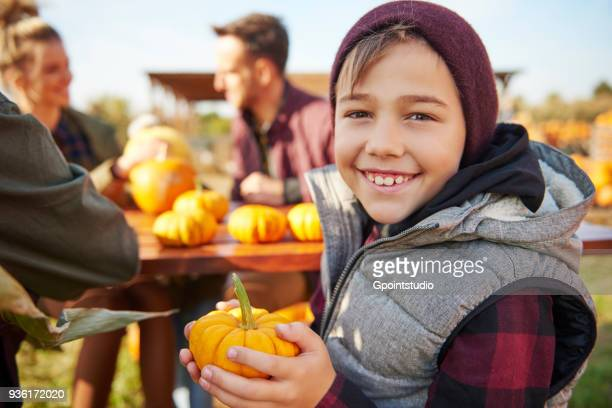 portrait of boy holding harvested vegetable squash - pumpkin patch stock photos and pictures
