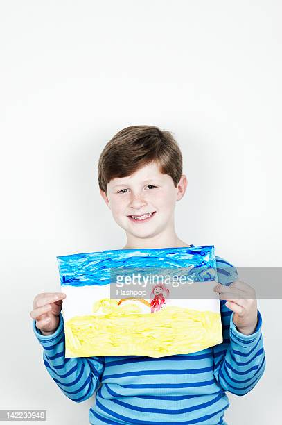 Portrait of boy holding his painting
