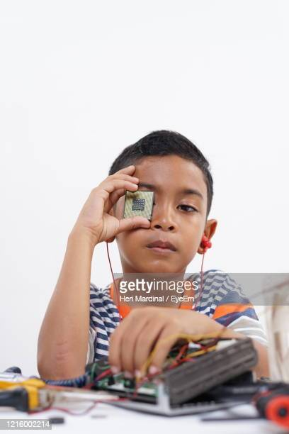 portrait of boy holding mobile phone - heri mardinal stock pictures, royalty-free photos & images