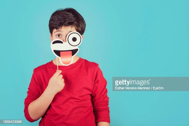 portrait of boy holding prop while standing against blue background - prop stock photos and pictures