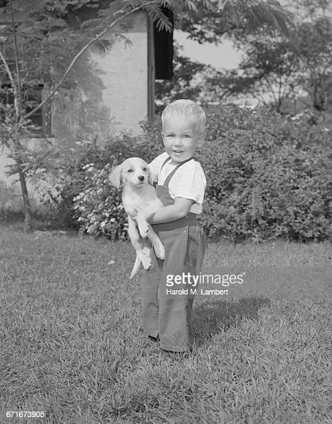 portrait of boy holding puppy - mamífero con garras fotografías e imágenes de stock