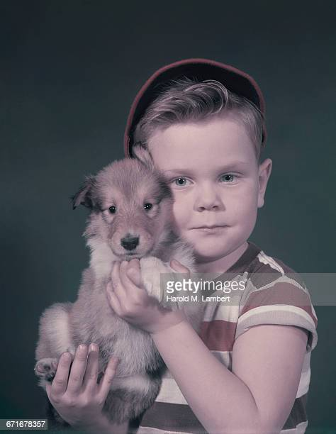 portrait of boy holding puppy  - pawed mammal stock pictures, royalty-free photos & images