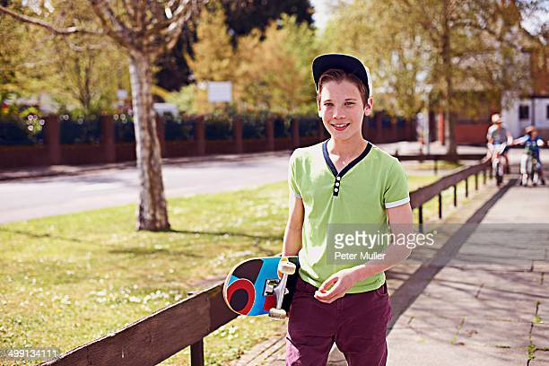 Portrait of boy holding skateboard