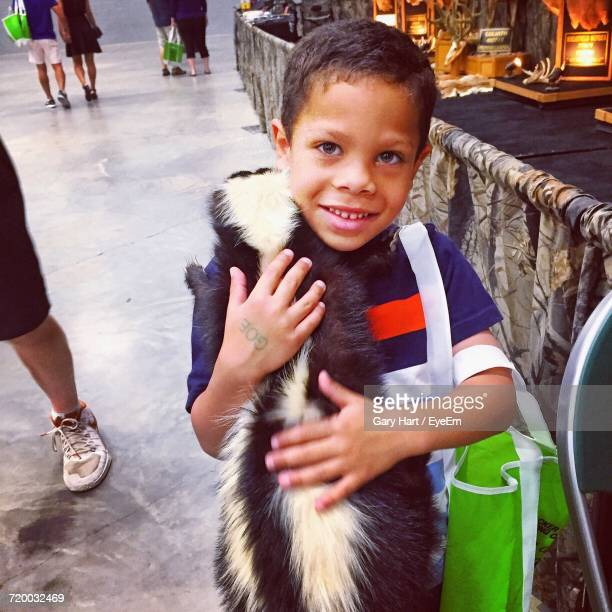 portrait of boy holding skunk in shopping mall - skunk stock photos and pictures