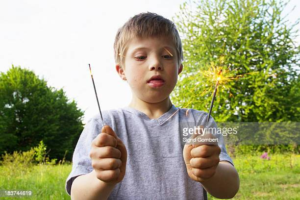 portrait of boy holding sparklers - sigrid gombert stock pictures, royalty-free photos & images