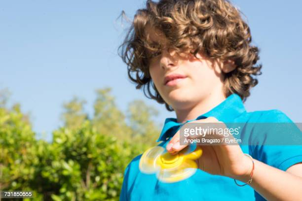 Portrait Of Boy Holding Spinner While Standing Against Sky
