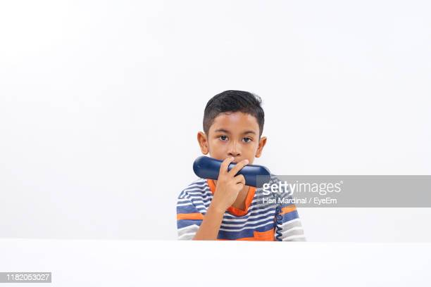 portrait of boy holding telephone receiver against white background - heri mardinal stock pictures, royalty-free photos & images