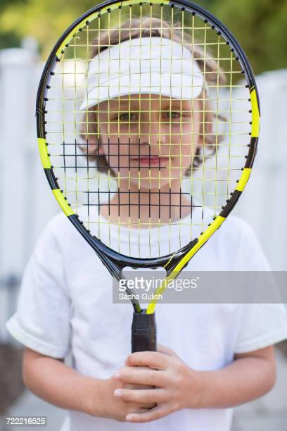 Portrait of boy holding tennis racket in front of face