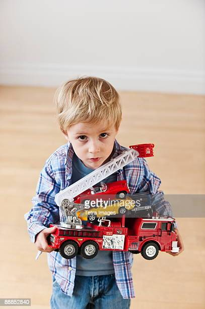 Portrait of boy (4-5) holding toy fire engine and cars