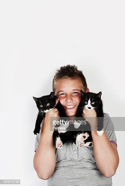 Portrait of boy holding two kittens