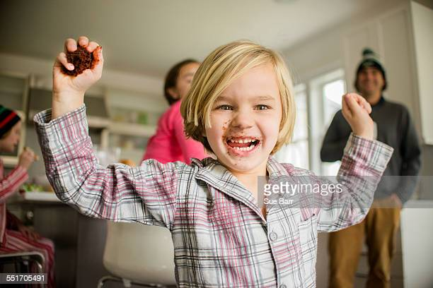 Portrait of boy holding up handful of cranberries in kitchen