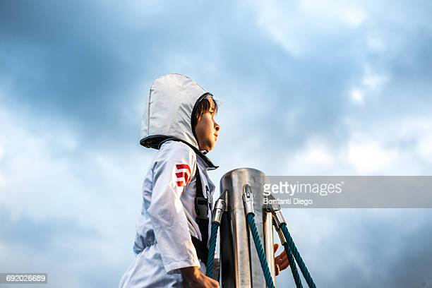 Portrait of boy in astronaut costume gazing out from top of climbing frame against dramatic sky
