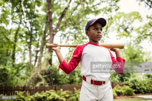 portrait of boy in baseball uniform outdoors - sports uniform stockfoto's en -beelden