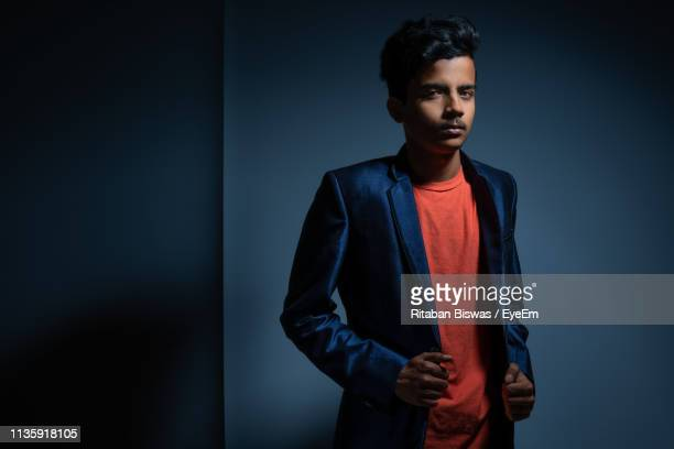 portrait of boy in blazer standing against wall - blue blazer stock pictures, royalty-free photos & images