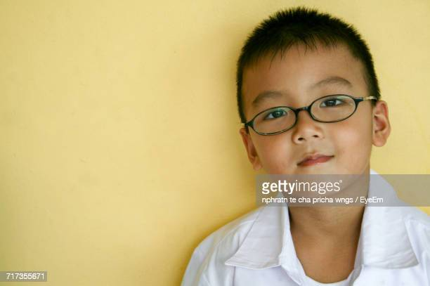Portrait Of Boy In Eyeglasses Against Yellow Wall At Home