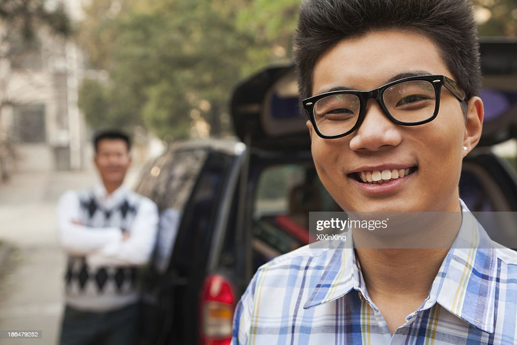 Portrait of boy in front of car on college campus : Stock Photo