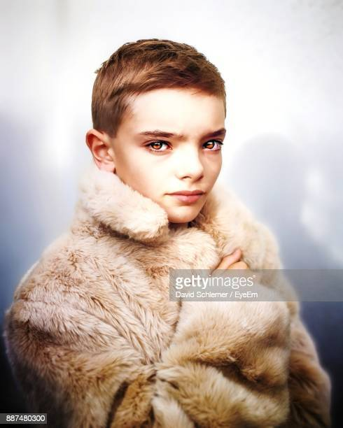 Portrait Of Boy In Fur Coat Against Colored Background