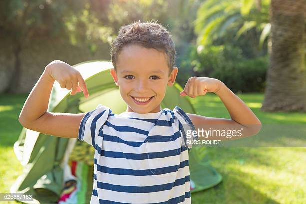 Portrait of boy in garden flexing muscles