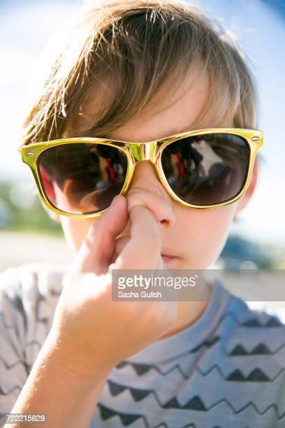 Portrait of boy in golden sunglasses picking his nose