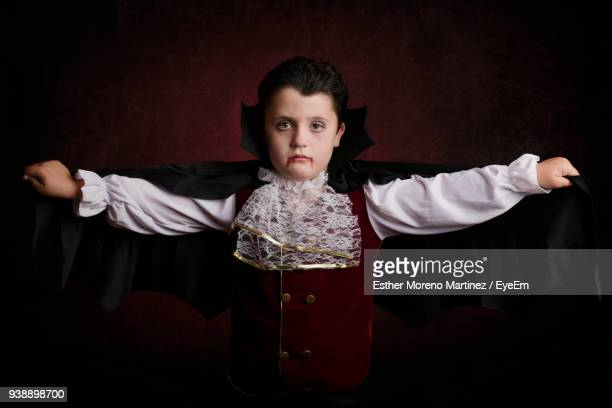 portrait of boy in halloween costume standing against wall - vampire stock pictures, royalty-free photos & images
