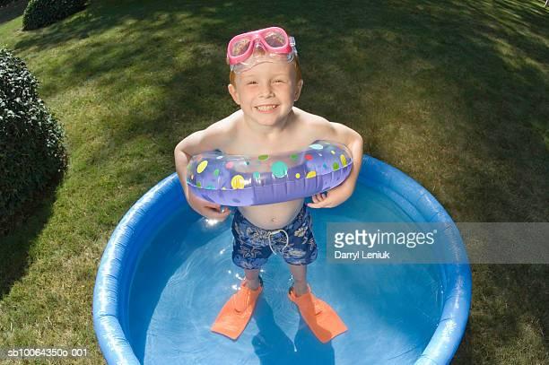 Portrait of boy (4-5) in kiddie pool, smiling