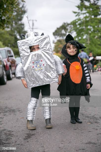 portrait of boy in robot costume and girl in witch costume on street - sasha gray stock photos and pictures