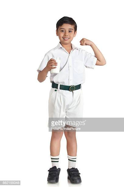 Portrait of boy in school uniform flexing muscles while holding milk over white background