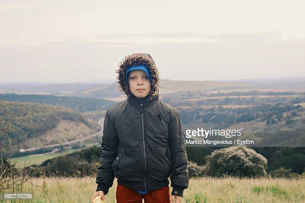 Portrait Of Boy In Winter Coat By Landscape Against Sky