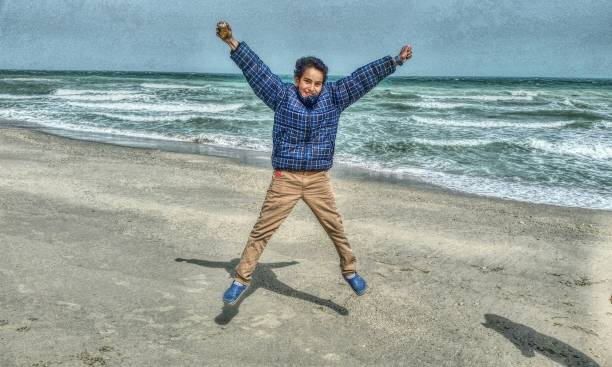 Portrait Of Boy Jumping At Beach