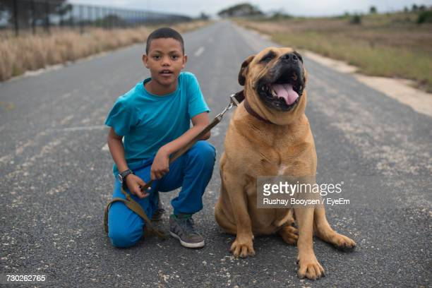 Portrait Of Boy Kneeling By Boerboel Dog On Road