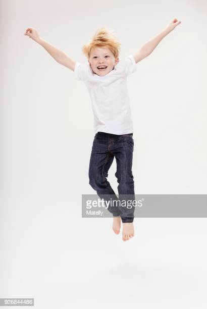 portrait of boy leaping in air - alleen jongens stockfoto's en -beelden