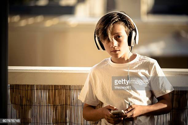 Portrait of boy listening music with headphones and smartphone on balcony